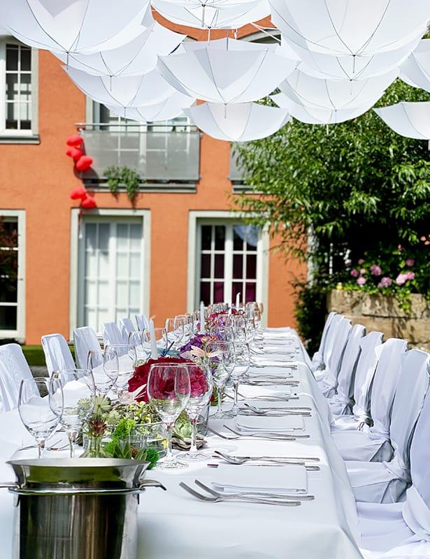 Hochzeit Catering weiße Sonnenschirme am Himmel unten festlich dekorierter edel eingedeckter Tisch mit unterschiedlichen Blumengestecken weiße Stühle mit Hussen auf Rasen im Hintergrund oranges Haus