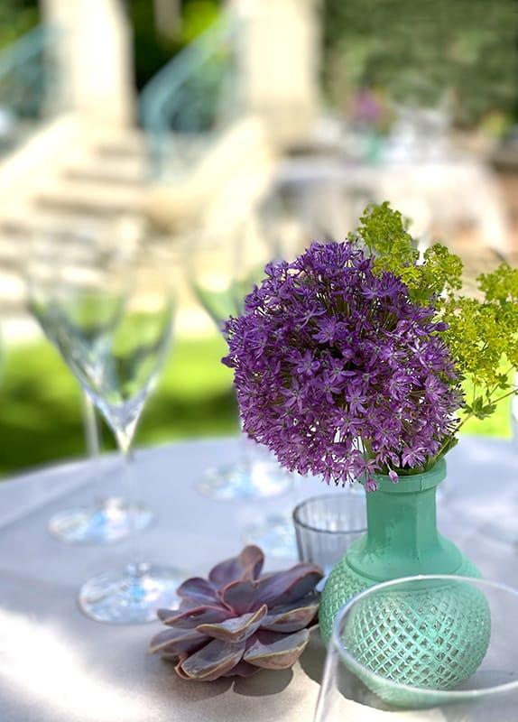 Nahaufnahme Stehtisch im Garten mit Tannenzapfen Blumenvase mit Lauchblume und unscharf im Hintergrund Gläser Treppe Menschen